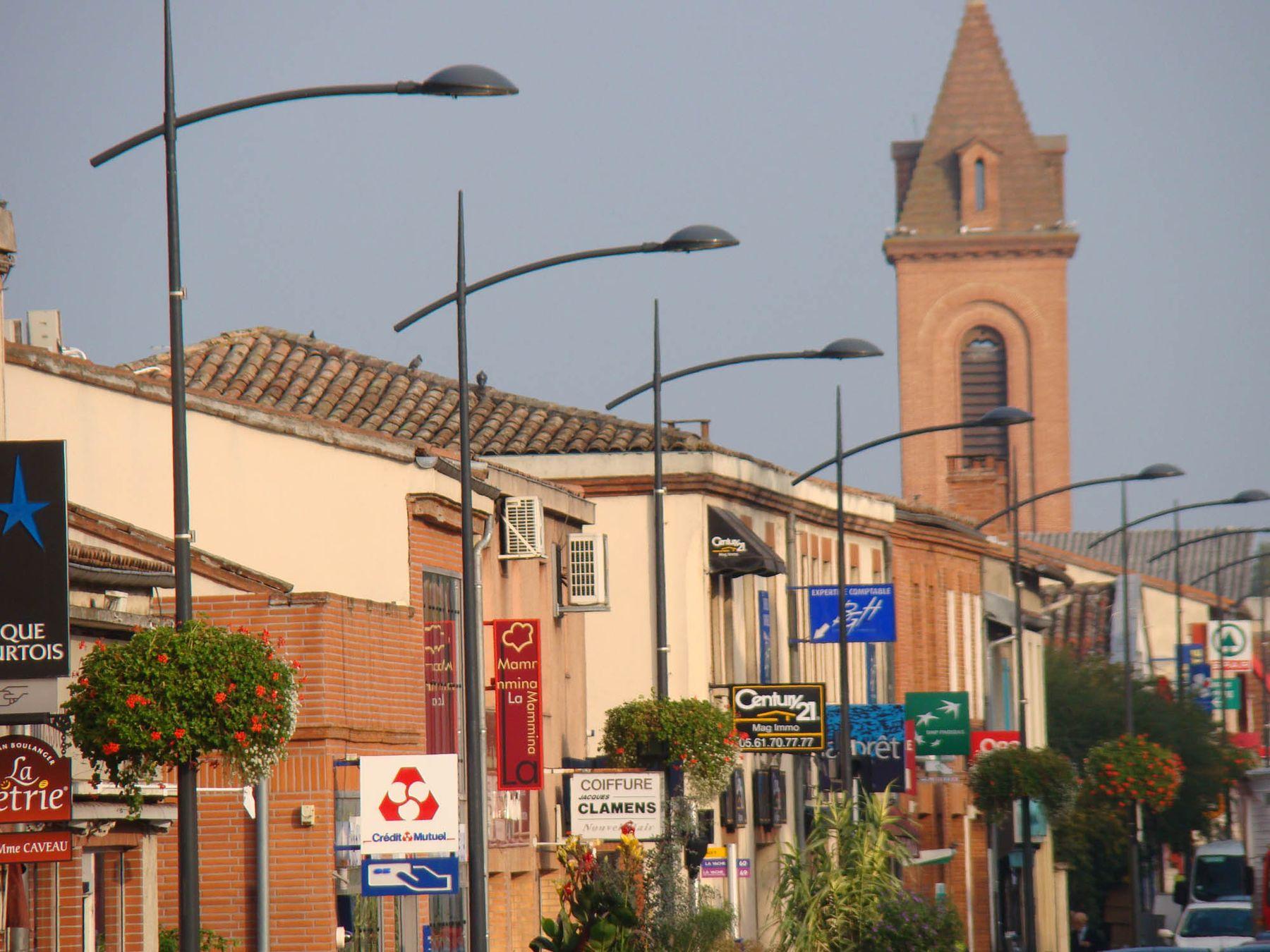 façades commerçantes et clocher de l'église route de Fronton